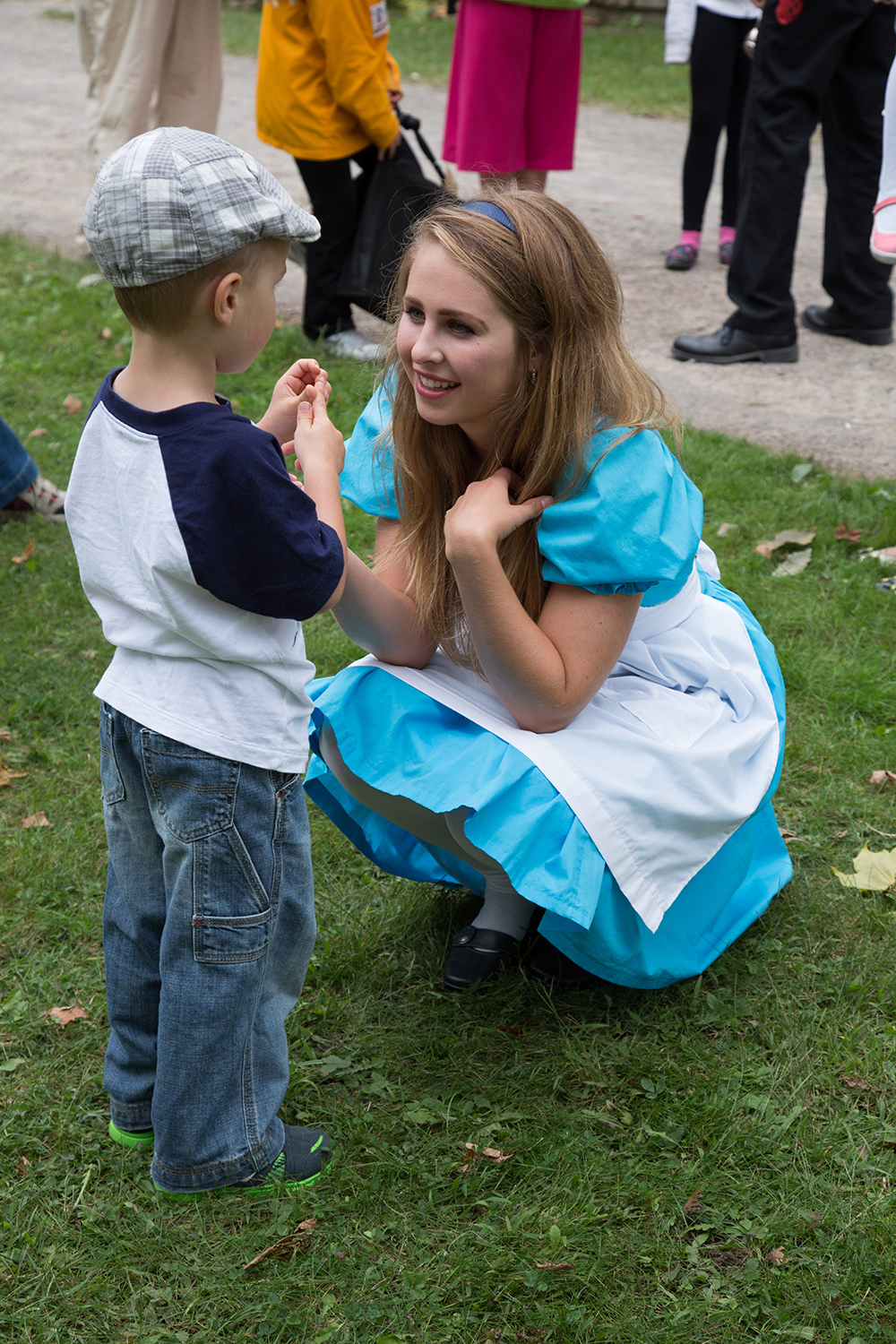 Young boy standing next to a young woman dressed as Alice in Wonderland