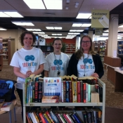 three HPL staff wearing 100In1Day shirts in the library