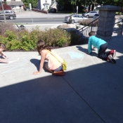 Three children drawing with chalk outisde the Ancaster branch