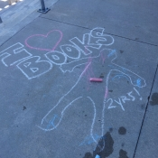 Chalk drawing of a child's outline with I heart books written above