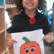 girl holding a pumpkin colouring sheet