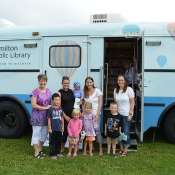 A group of parents and children standing in front of the HPL Bookmobile at Summit Park in June 2015