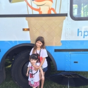 Two girls stand infront of the Bookmobile wheel in Bayfront Park
