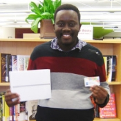 man holding an ipad and library card
