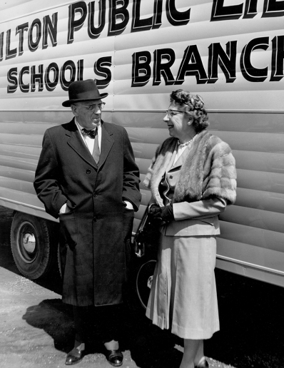 Archival photo of Mayor Lloyd D. Jackson and Freda Waldon, Chief Librarian standing next to the Bookmobile in 1961