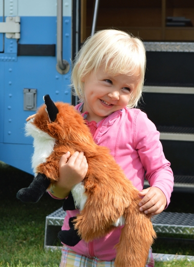 Photo of a little girl holding a fox puppet at the steps of the HPL Bookmobile