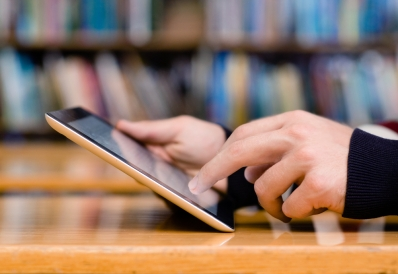 Closeup of hands holding a tablet with books in the background