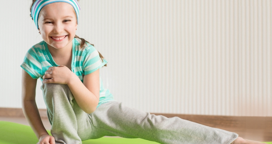 Young girl in exercise clothes stretching on a yoga mat