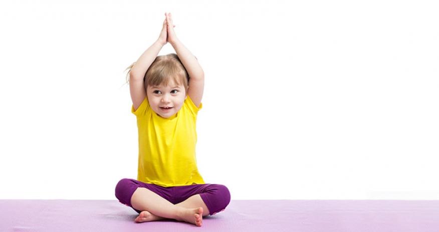 toddler girl sitting on a yoga mat