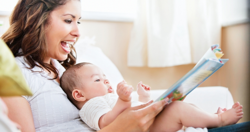 Mother reading a book to her baby that is sitting in her lap