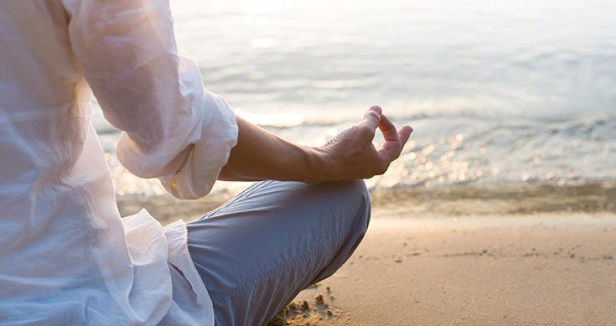 female meditating on a beach