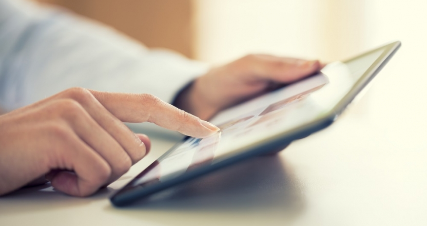 Closeup of woman's hands holding an iPad