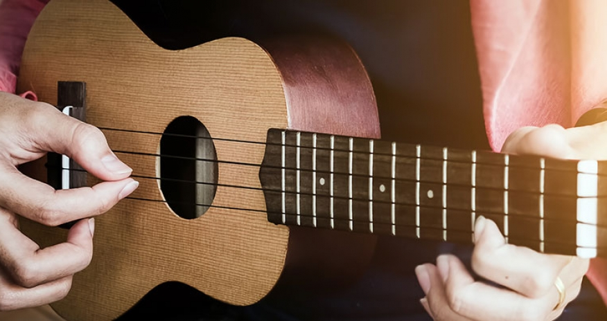 female playing ukulele